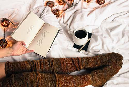 book mug of black coffee beside person's feet wearing brown stockigns coffee