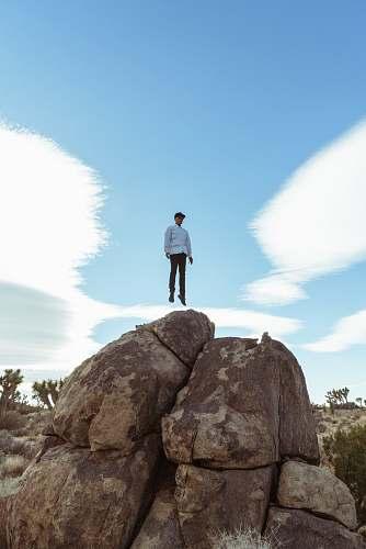 blue man jump on brown boulder joshua tree