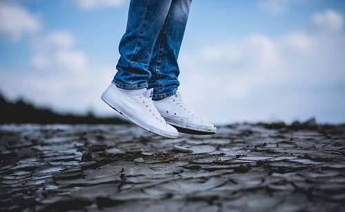 blue person wearing white low-top sneakers jump