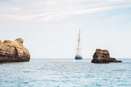 rock blue boat between brown rock formation under blue and white sky at daytime ocean
