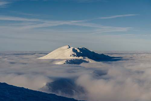 winter white mountain surrounded gray clouds under blue sky snow