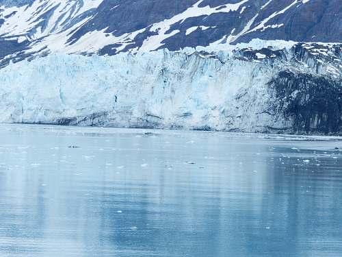 mountain mountain reflecting on body of water glacier