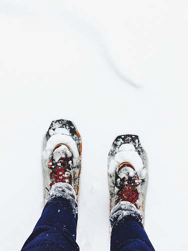 winter person wearing blue jeans standing on snow shoe