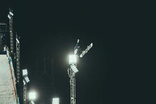 snow person snowboarding making stunts during nighttime sports