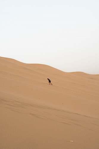 nature man climbing sand dunes outdoors