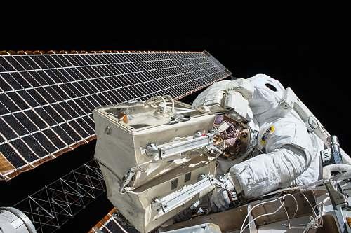 nasa closeup photo of astronaut repairing satellite astronaut