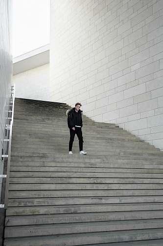 handrail man walking near stairway during daytime banister
