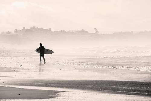 beach silhouette person walking on sandbank while holding surfboard sports