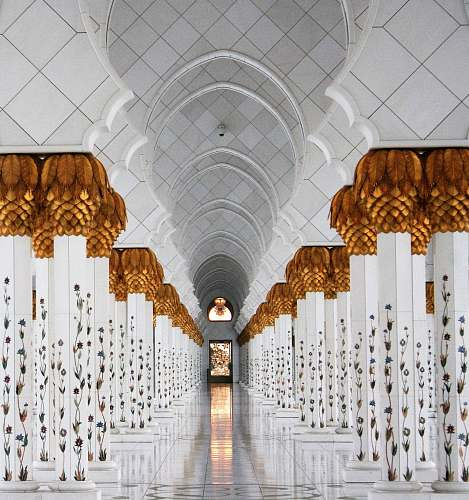 architecture photo of white columns and marble tiles mosque