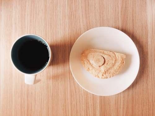 cup mug full of black coffee near a slice of cake coffee cup