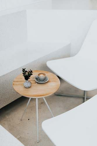 furniture round brown table beside two white chairs coffee table