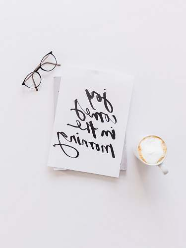 handwriting brown framed eyeglasses,latte, and joy comes in the morning note on white surface calligraphy