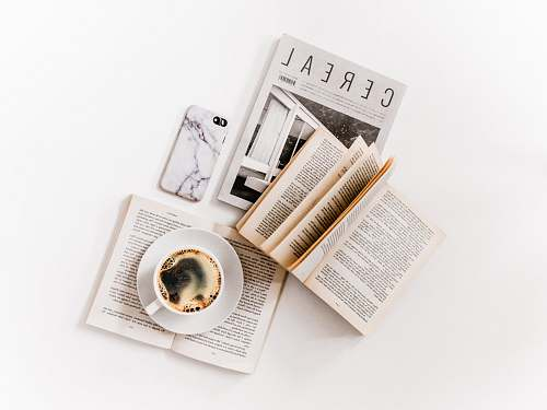 page white ceramic cup with coffee on saucer beside opened books white