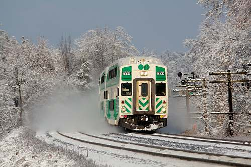 transportation white and green train on railway during daytime vehicle