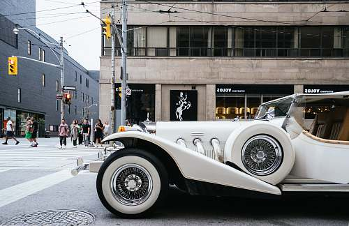 car photo of classic white vehicle near pedestrian lane automobile