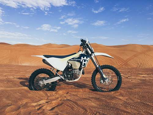 motorcycle black and white dirt bike on sand blue