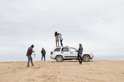 car two people standing on Jeep Grand Cherokee SUV while the other person camera on sand during daytime transportation