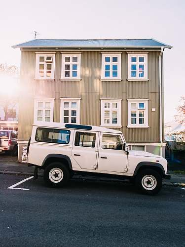 windows white vehicle near beige house jeep