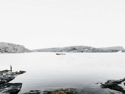 shoreline boat on body of water near island sea