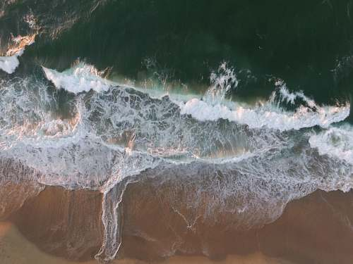 sea body of water splashing on a sand ocean