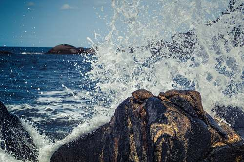 sea seawater splashing rock boulders at daytime nature