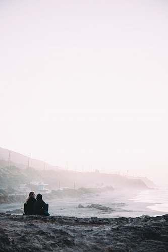 malibu two person sitting beside shore coast
