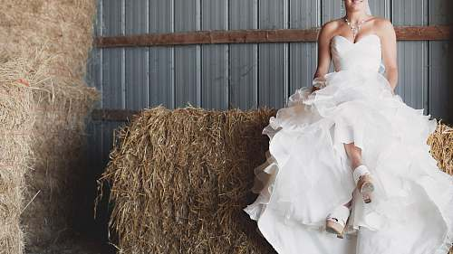 person woman in ruffled wedding gown sitting on haystack human