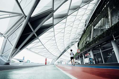 architecture person running on field during daytime airport terminal