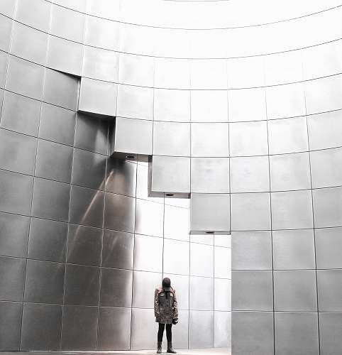 black-and-white person standing under metal block building wall