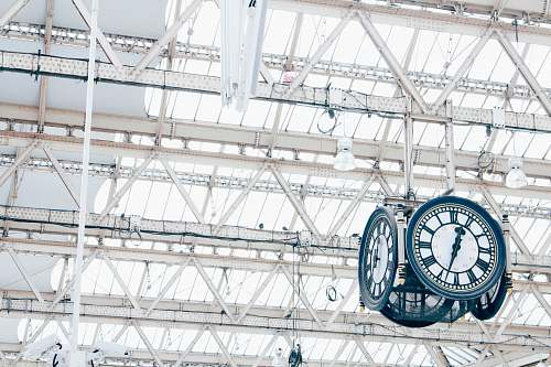 scaffolding round white and blue analog hanging clock under white trusses construction