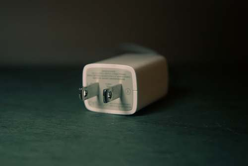 plug shallow focus photography of white travel adapter charger