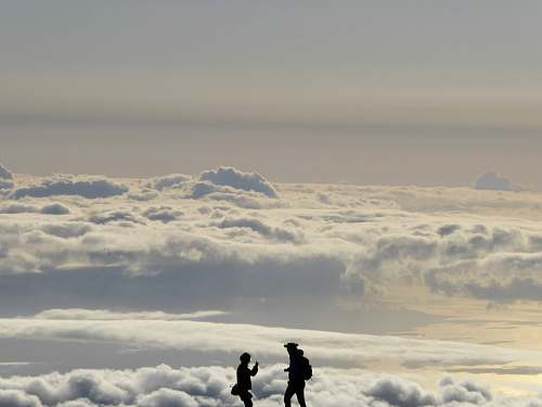 cloud silhouette of two people overlooking clouds during daytime sky