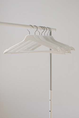grey white clothes hangers hanging on rack home