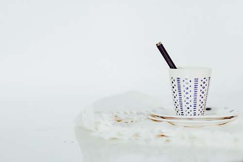 minimal white cup with pen on white panel coffee