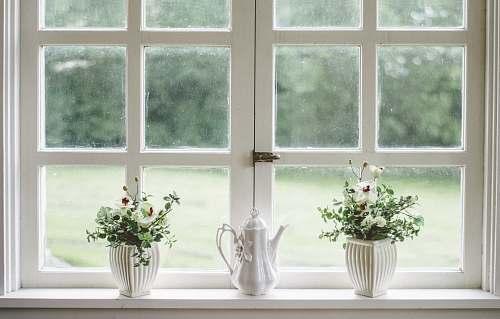 interior white teapot and tow flower vases on windowpane window