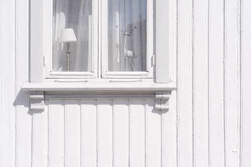 norway white wooden wall cabinet with figurine and table lamp inside light