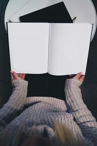 book woman wearing sweater opening blank book grey
