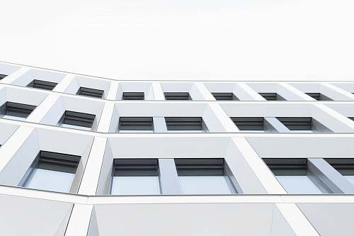 building worm's eyeview photo of white concrete 3-storey building window