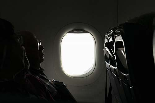 porthole two person sitting inside of airplane passenger