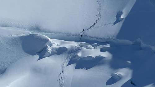 snow aerial photography of group of people trekking on snow mountain