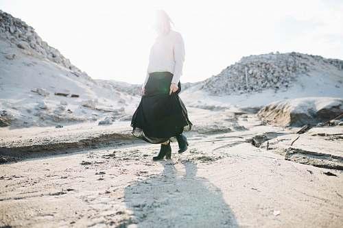 skirt woman in black skirt walking on gray flooring fashion