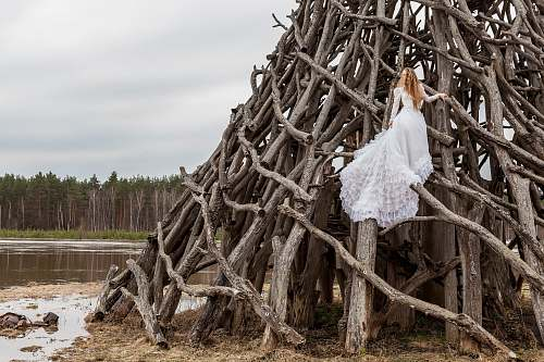 wood woman in white dress on piled wood logs river