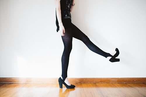 female woman raising her right leg near wall shoe