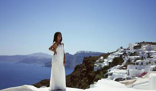 dress woman wearing white dress in front building beside sea greece