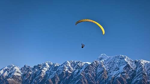 paraglide man on parachute near the mountain paragliding