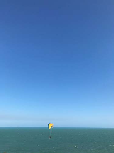 leisure activities person paragliding above blue sea during daytime gliding