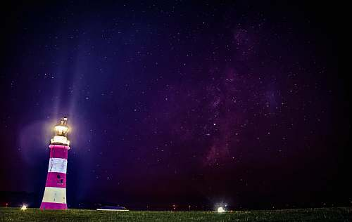 blue lighthouse turned on near green grass field smeaton's tower