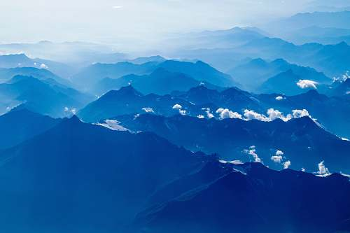 nature aerial photography of mountain under clear blue sky mountain