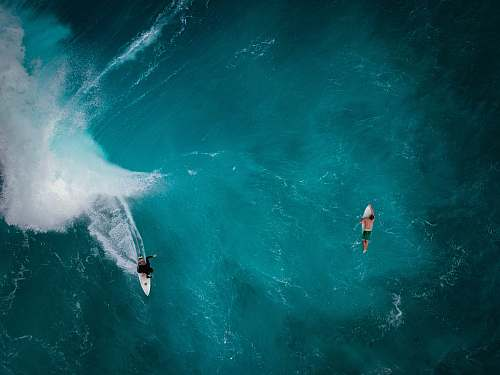 ocean aerial photography of two persons surfing sea