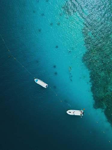 malaysia aerial photography of two white motor boats on calm body of sea pulau sapi